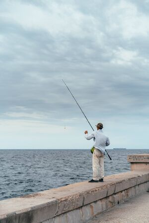 Fisherman with fishing rod on the concrete embankment of the Caribbean in Havana Stock Photo