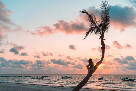 Girl sitting on a palm tree at sunrise on the sandy beach of the Caribbean in Mexico