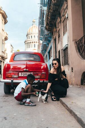 A girl in black clothes and a boy stroking a black and white cat next to a red retro car on the background of the capitol in old Havana