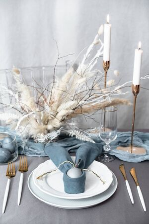 Setting Easter table with candles and colored eggs