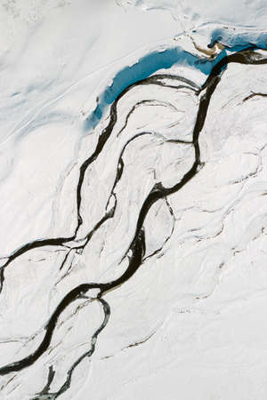 Drone view of the winding river among the snow-covered steppe in winter
