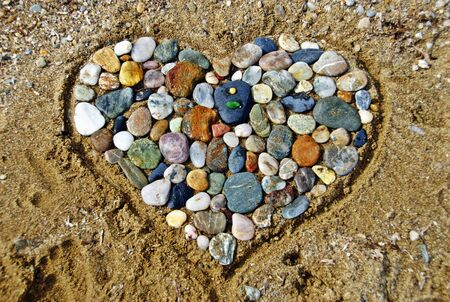 Heart-shaped sand sculpture filled with stones on the beach at Papakostas bay of Agiokampos town. Thessaly region, central Greece.