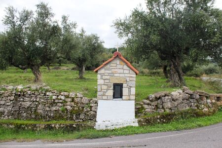 A small country iconostasis, church-like small-scale replica for candle-lighting with olive grove in the background in Messinia region, southwestern Greece.