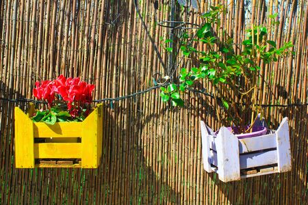 Decorative wooden crates on a garden's fence.