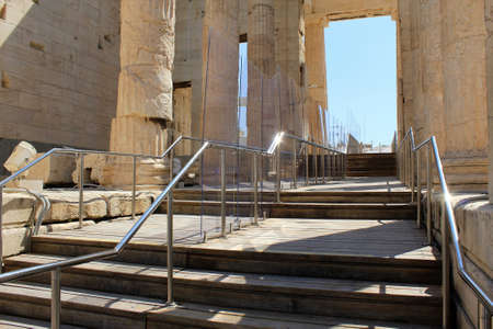 Greece, Athens, July 16 2020 - View of Propylaea, the monumental entrance to the Acropolis of Athens, empty of visitors. Plexiglass separators have been installed following a long list of new safety rules due to coronavirus outbreak. Tourism has been the
