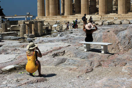 Greece, Athens, July 16 2020 - Tourists taking pictures at the archaeological site of Acropolis hill with Parthenon temple in the background. 新闻类图片