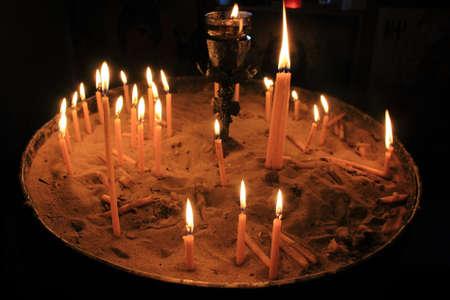 Lighting candles inside a Greek orthodox church. Stock fotó