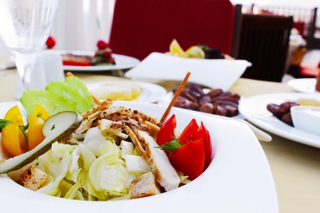 Mediterranean salad with chicken decorated on table photo
