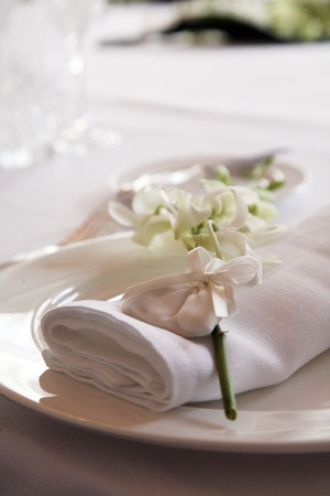 Detail of a wedding dinner plate with white napkin and wedding favor on top of it Reklamní fotografie