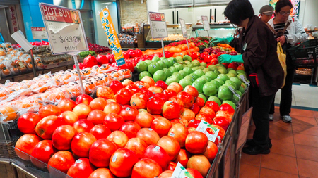 Woman selecting fresh red apples in grocery store produce department and putting it in plastic bag. Young pretty girl is choosing apples in supermarket and putting them into shop basket. Close up Editorial