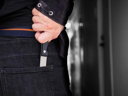 背中の後ろにナイフを持った危険男 写真素材