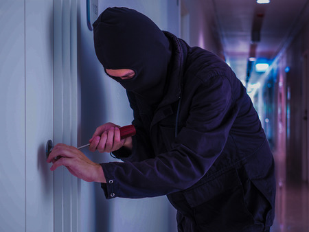breaking: Security - Disguised Burglar Breaking In An Apartment Or Office To Steal Something Stock Photo