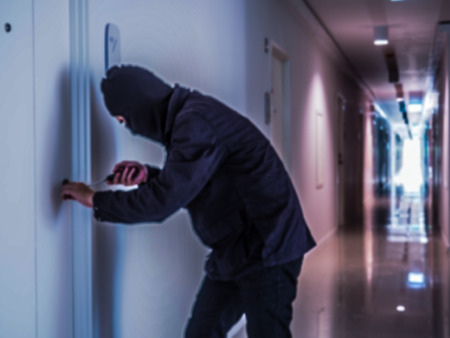 Blurred image of  Burglar wearing black clothes and breaking in the apartment at noon Stock Photo
