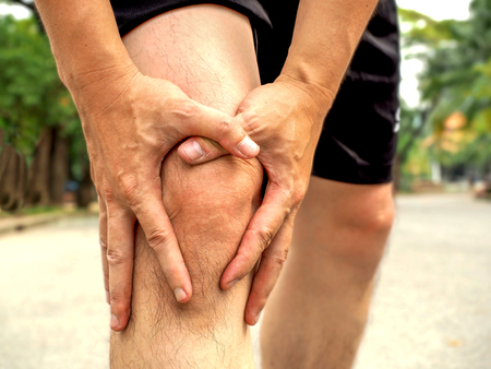 People with knee pain and feeling bad hand on he knee, healthy concept.