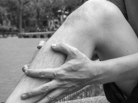 Running sport injury. male athlete jogger wearing man runner massaging calf muscle before workout. Stock Photo