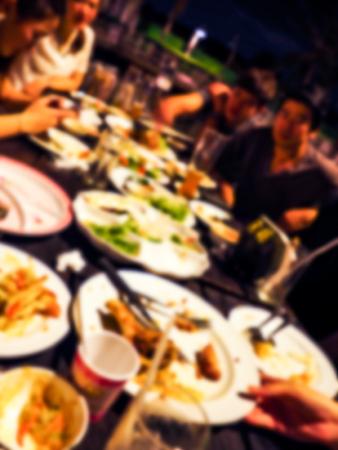 Immagine sfocata della festa degli amici, sedersi e mangiare insieme. Sono seduti a un tavolo di legno con birre e cibo tailandese.