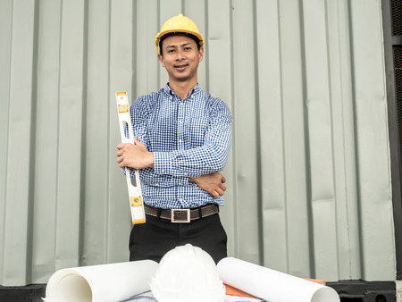 Portrait of an Engineer man holding level measuring instrument and standing at container box background