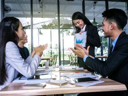 Business team applauding colleague at a meeting 版權商用圖片