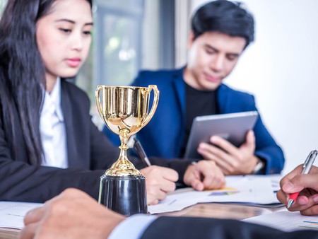 Businessman with teamwork in goal and successful trophy and rewarded for in the office Stock Photo