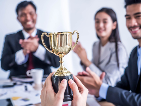 Businessman with teamwork in goal and successful showing trophy and rewarded for in the office