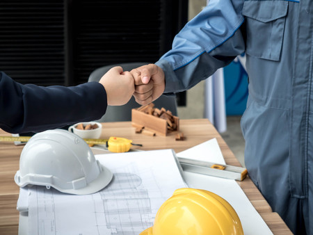 business, building, teamwork, gesture and people concept - group of smiling builders in hardhats greeting each other with Hand collision.