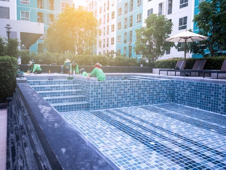직원들이 수영장을 청소하고 있습니다.