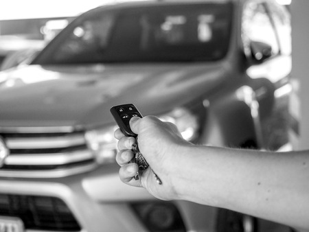hand open the car with car remote key at car park.