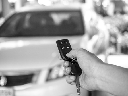 Mans hand open the car with car remote key at car park. Stock Photo
