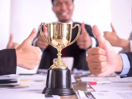 Businessman with teamwork in goal and successful showing trophy and thumb up rewarded for in the office