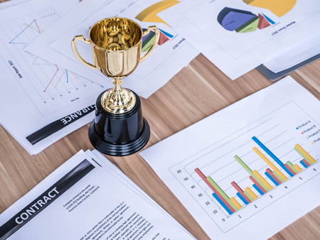 Award trophy on working table with document and contract