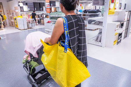 BANGKOK THAILAND - DECEMBER 25, 2016: De vrouw die met Grote gele het winkelen zakken in IKEA-Opslag winkelt. IKEA is 's werelds grootste meubelverkoper, opgericht in 1943 in Zweden Redactioneel