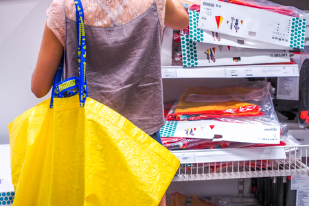 BANGKOK THAILAND - DECEMBER 25, 2016: The woman shopping with Big yellow shopping bags in IKEA Store. IKEA is the worlds largest furniture retailer, founded in Sweden in 1943