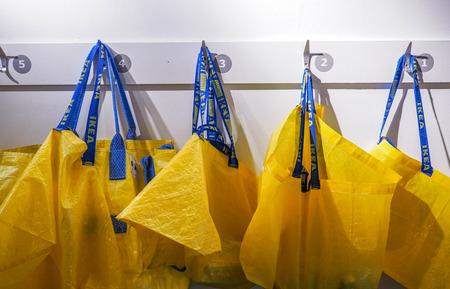 Grote gele boodschappentassen in de IKEA-winkel hangen aan de witte muren.