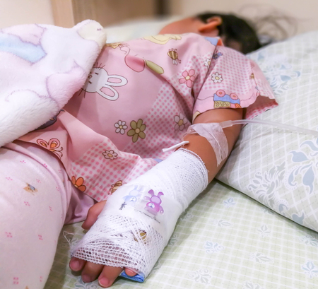 Asian kid patient, Close up of iv plug in patient's child hand.heparin lock in hospital with saline intravenous (IV) drip
