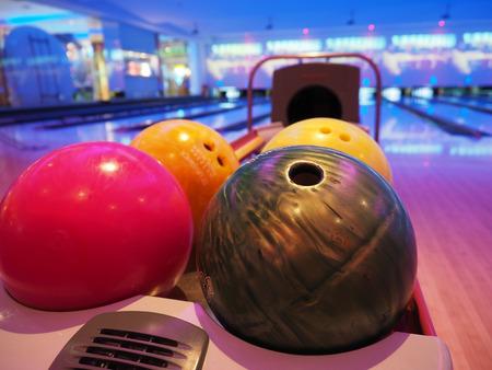 Bowling-Hintergrund. Innenraum des Bowlingbahnweges mit Bällen geben Maschinennahaufnahme, selektiven Fokus auf blauem Ball zurück