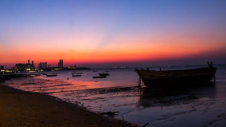 Fishing boats at coastal in sunset. The back of Pattaya city.