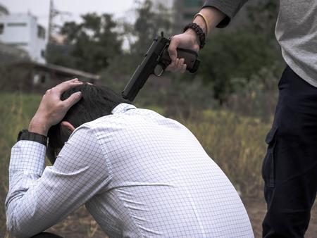 Portrait of Killer hand holding gun and put gun to businessman head. Stock Photo