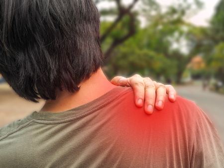 people, healthcare and problem concept - unhappy man suffering from neck or shoulder pain at park