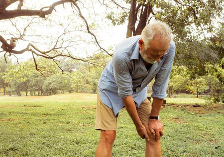 Verouderende man met pijn in zijn knie op het park, pijn bij ouderen, gezondheidszorg