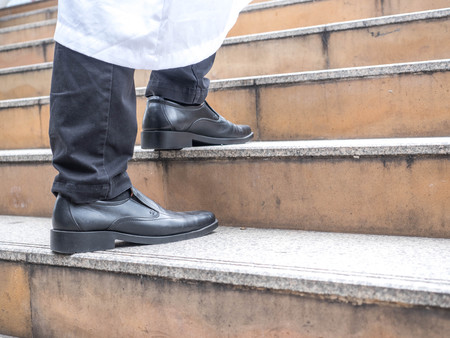 close up of businessman legs walk up the stone staircase. Arab businessman