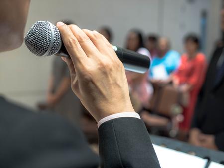 hombre que sostiene el micrófono en la mano, Ponente en la conferencia.