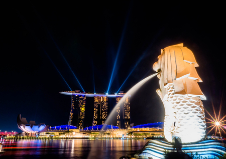 SINGAPORE - NOV 22, 2018: The Merlion fountain spouts water in front of the Marina Bay Sands hotel in Singapore. This fountain is one of most well known icons of Singapore