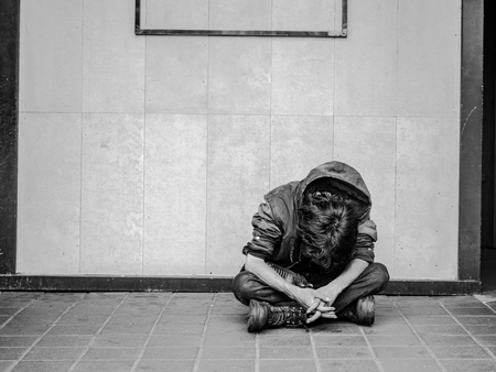 An unidentified homeless man begging for help and money. Problems of big modern cities. Stock Photo