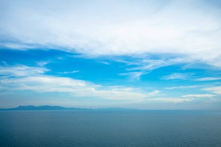 Beautiful white clouds on blue sky over calm sea with sunlight reflection