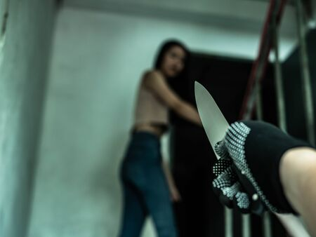 Unknown criminal guy with knife chasing young girl. Robbery or rape in gangster district concept, a person or thing that is likely to cause harm, a threat or danger.