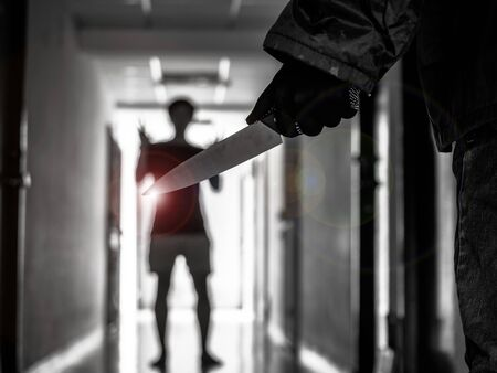 Hand with knife following young terrified in the apartment. man Bandit is holding a knife in hand, Threat Concept, Murder concept
