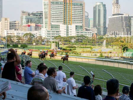 Bangkok, Thailand - Feb 24, 2019: Group of horses charging for the finish line during racing day at The Royal Bangkok Sports Club.