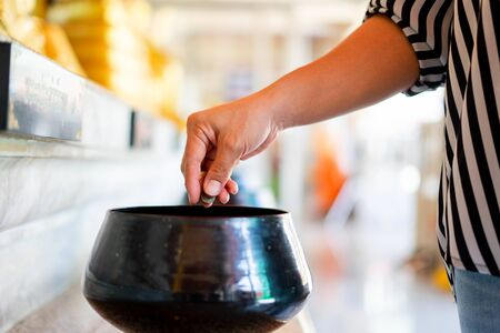 A hand putting coins in one of monk alms bowl for merit in buddhism with lots of monk alms bowls beside in a temple, The coin in monks bowl or almsbowl.