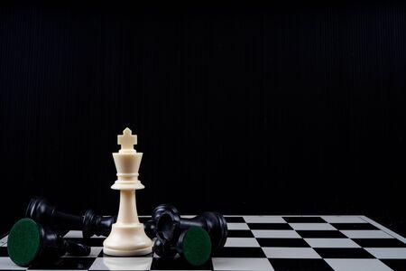 Le roi d'échecs debout gagne le jeu de configuration d'échecs sur fond sombre. Le concept d'échecs sauve le roi et sauve la stratégie, le jeu est terminé.