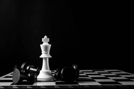 Le roi d'échecs debout gagne le jeu de configuration d'échecs sur fond sombre. Le concept d'échecs sauve le roi et sauve la stratégie, le jeu est terminé. Banque d'images